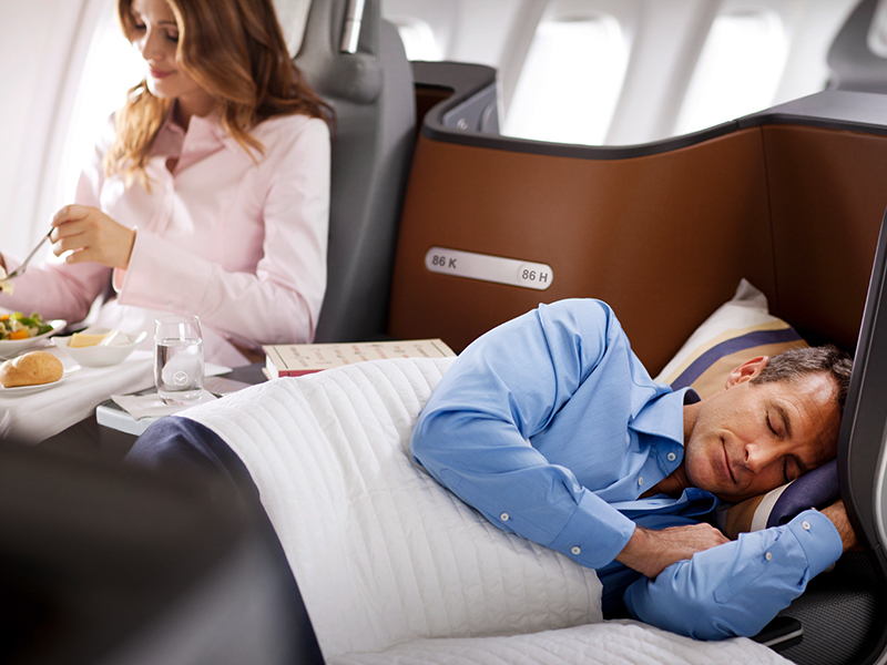 man sleeping in business class travel